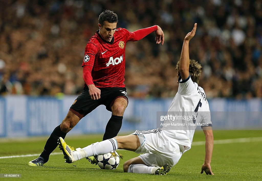 Robin van Persie of Manchester United is challenged by Fabio Coentrao of Real Madrid during the UEFA Champions League Round of 16 first leg match between Real Madrid and Manchester United at Estadio Santiago Bernabeu on February 13, 2013 in Madrid, Spain.