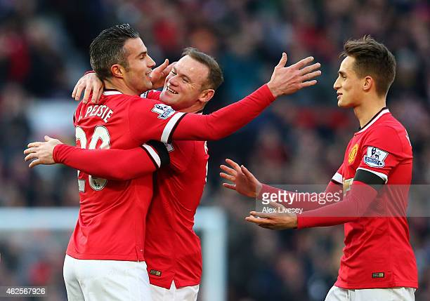 Robin van Persie of Manchester United is congratulated by teammates Wayne Rooney and Adnan Januzaj after scoring his team's first goal during the...