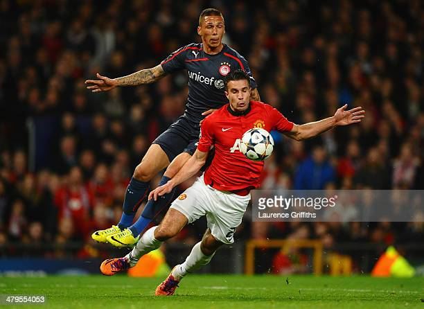 Robin van Persie of Manchester United is fouled in the penalty box by Jose Holebas of Olympiacos during the UEFA Champions League Round of 16 second...