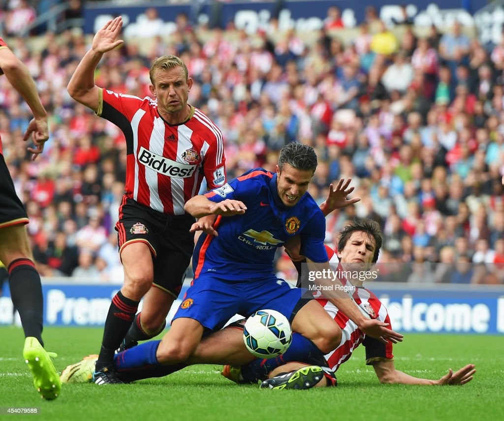 Robin van Persie of Manchester United is tackled by Lee Cattermole (L) and Santiago Vergini of Sunderland during the Barclays Premier League match between Sunderland and Manchester United at Stadium of Light on August 24, 2014 in Sunderland, England.