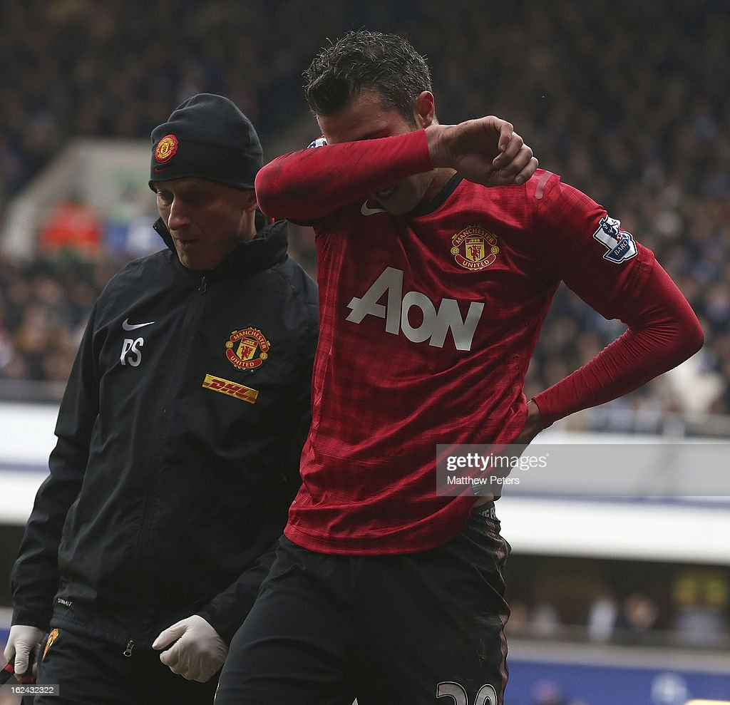 Robin van Persie of Manchester United leaves the pitch with an injury after colliding with a TV camera during the Barclays Premier League match between Queens Park Rangers and Manchester United at Loftus Road on February 23, 2013 in London, England.