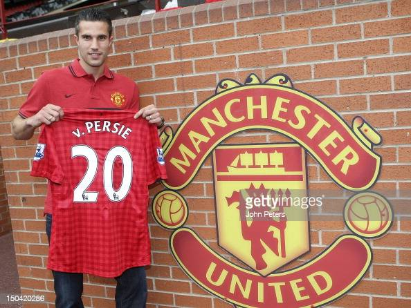 Robin van Persie of Manchester United poses with a Manchester United shirt after signing a four year contract with the club at Old Trafford on August...