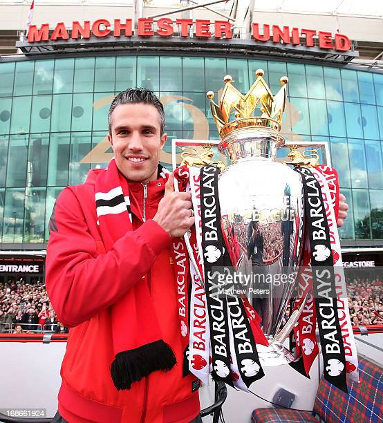 Robin van Persie of Manchester United poses with the Premier League trophy at the start of the Premier League trophy winners parade on May 13 2013 in...