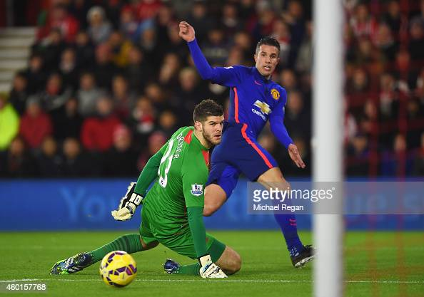 Robin van Persie of Manchester United scores past Fraser Forster of Southampton for the opening goal during the Barclays Premier League match between...