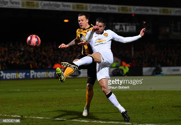Robin van Persie of Manchester United shoots at goal under pressure from Josh Coulson of Cambridge United during the FA Cup Fourth Round match...