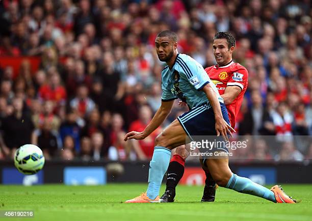 Robin van Persie of Manchester United shoots past Winston Reid of West Ham to score his team's second goal during the Barclays Premier League match...