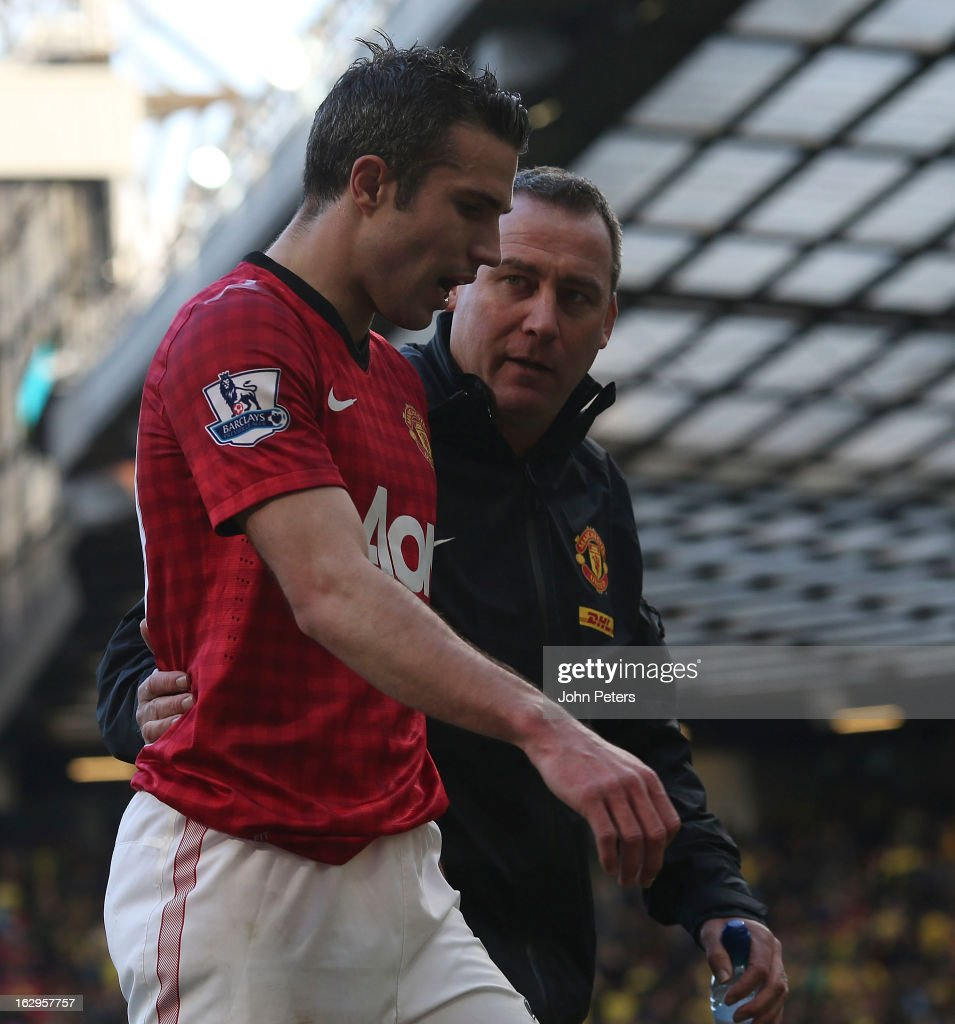 Robin van Persie of Manchester United speaks to first team coach Rene Meulensteen after picking up an injury during the Barclays Premier League match between Manchester United and Norwich City at Old Trafford on March 2, 2013 in Manchester, England.