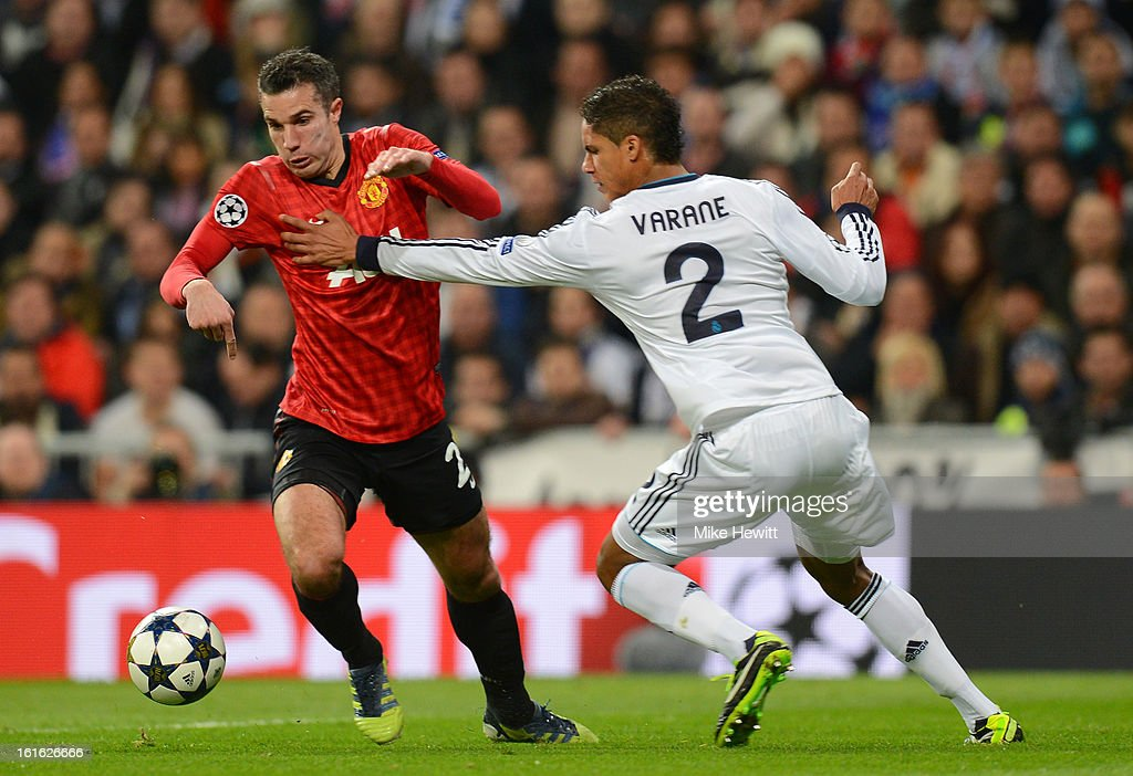 Robin van Persie of Manchester United tries to go past Raphael Varane of Real Madrid during the UEFA Champions League Round of 16 first leg match between Real Madrid and Manchester United at Estadio Santiago Bernabeu on February 13, 2013 in Madrid, Spain.