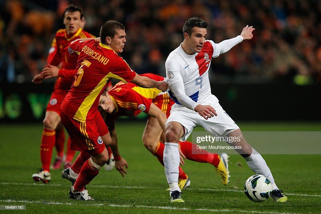 Robin Van Persie of Netherlands passes the ball past Alexandru Bourceanu of Romania during the the Group 4 FIFA 2014 World Cup Qualifier match between Netherlands and Romania at Amsterdam Arena on March 26, 2013 in Amsterdam, Netherlands.