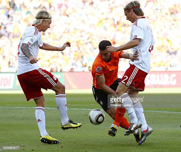 Robin Van Persie of the Netherlands attempts to run between Simon Kjaer and Christian Poulsen of Denmark during the 2010 FIFA World Cup Group E match...