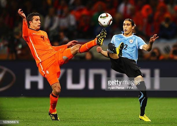 Robin Van Persie of the Netherlands battles for the ball with Martin Caceres of Uruguay during the 2010 FIFA World Cup South Africa Semi Final match...