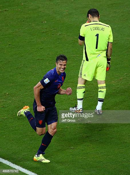 Robin van Persie of the Netherlands celebrates after scoring his second goal and his team's fourth as a dejected Iker Casillas of Spain looks on...