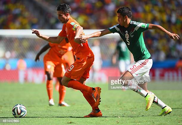 Robin van Persie of the Netherlands controls the ball against Diego Reyes of Mexico during the 2014 FIFA World Cup Brazil Round of 16 match between...