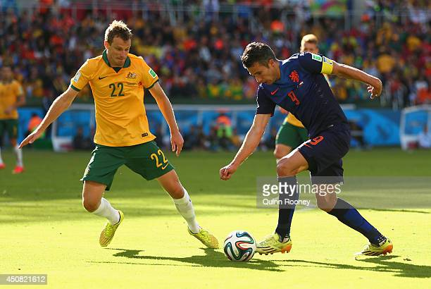 Robin van Persie of the Netherlands controls the ball as Alex Wilkinson of Australia gives chase during the 2014 FIFA World Cup Brazil Group B match...
