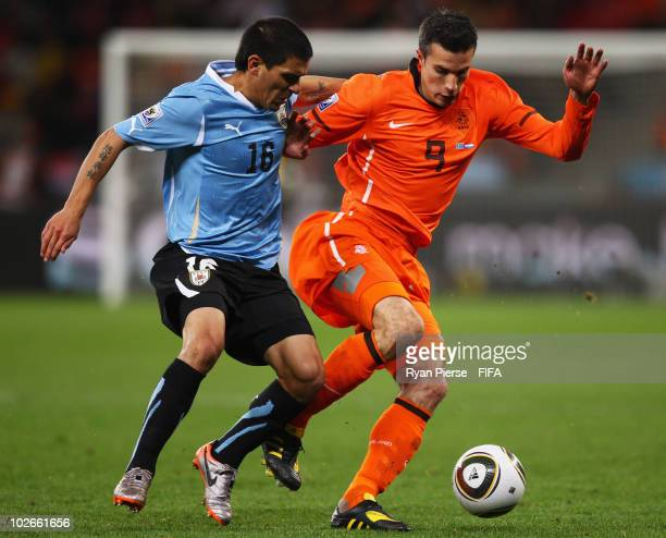 Robin Van Persie of the Netherlands in action against Ignacio Gonzalez of Uruguay during the 2010 FIFA World Cup South Africa Semi Final match...
