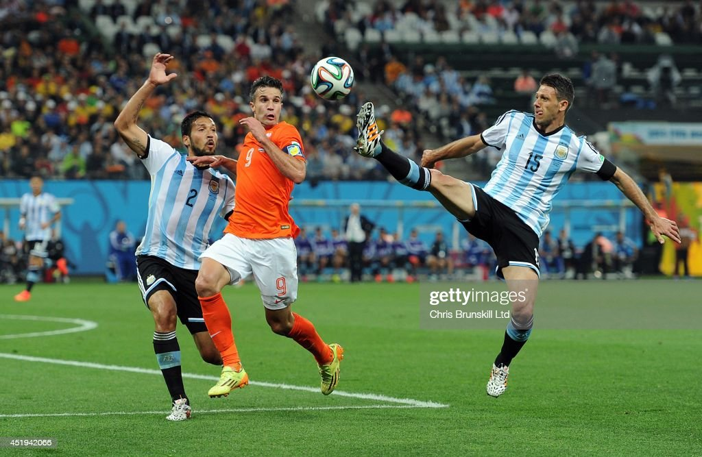 Robin Van Persie of the Netherlands in action with Ezequiel Garay (L) and Martin Dimichelis of Argentina during the 2014 FIFA World Cup Brazil Semi Final match between Netherlands and Argentina at Arena de Sao Paulo on July 09, 2014 in Sao Paulo, Brazil.