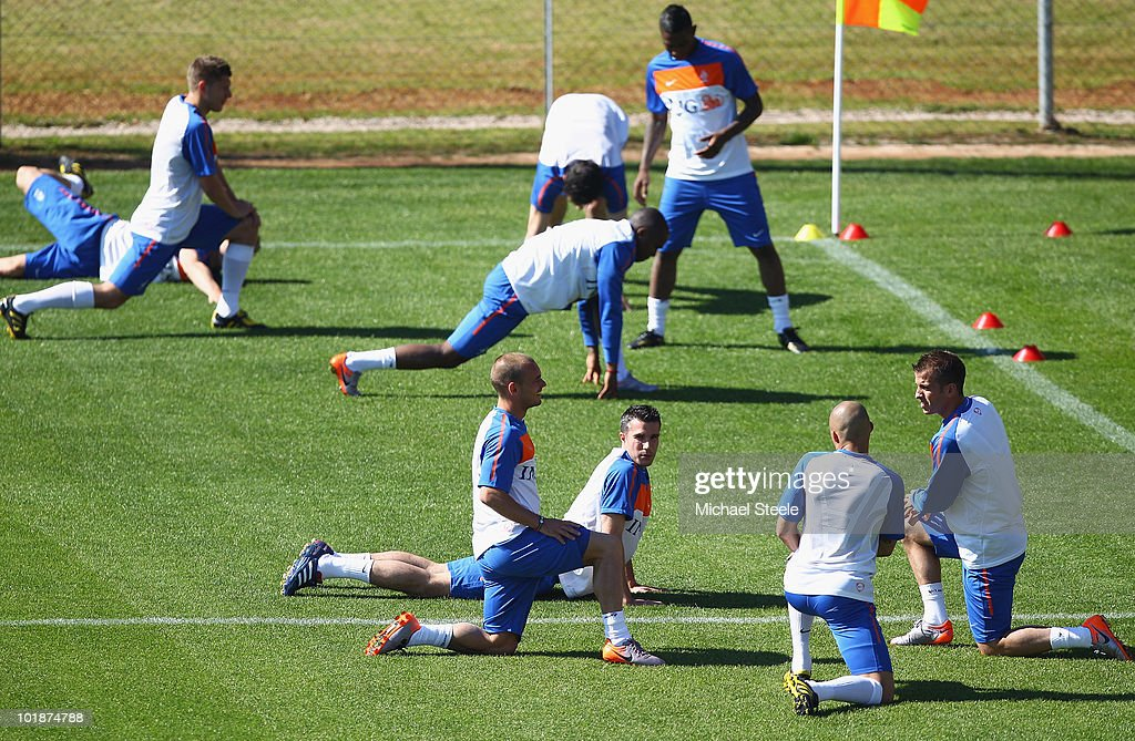 Robin van Persie (c) stretches as he looks towards Wesley Sneijder (l), Demy De Zeeuw (2nd r) and Rafael van der Vaart (r) during a Netherlands training session at the Wits Rugby Stadium on June 8, 2010 in Johannesburg, South Africa.
