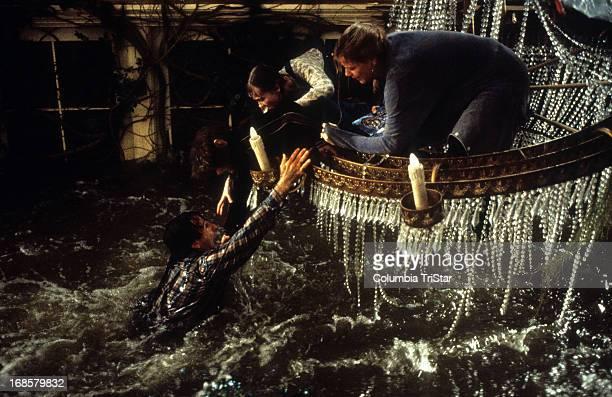 Robin Williams hangs onto Bradley Pierce Kirsten Dunst and Bonnie Hunt in a scene from the film 'Jumanji' 1995