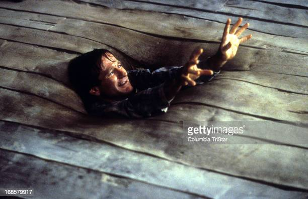 Robin Williams sinks into the floor in a scene from the film 'Jumanji' 1995