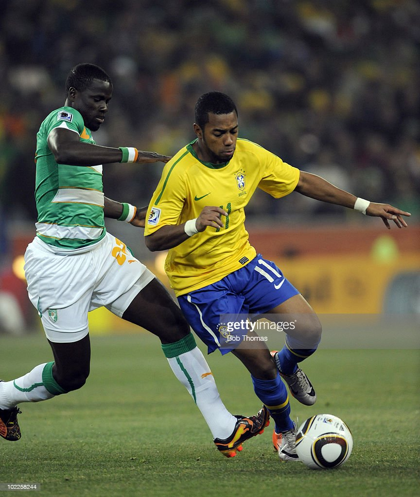 Robinho of Brazil challenged by Emmanuel Eboue of Ivory Coast during the 2010 FIFA World Cup South Africa Group G match between Brazil and Ivory Coast at Soccer City Stadium on June 20, 2010 in Johannesburg, South Africa. Brazil won the match 3-1.