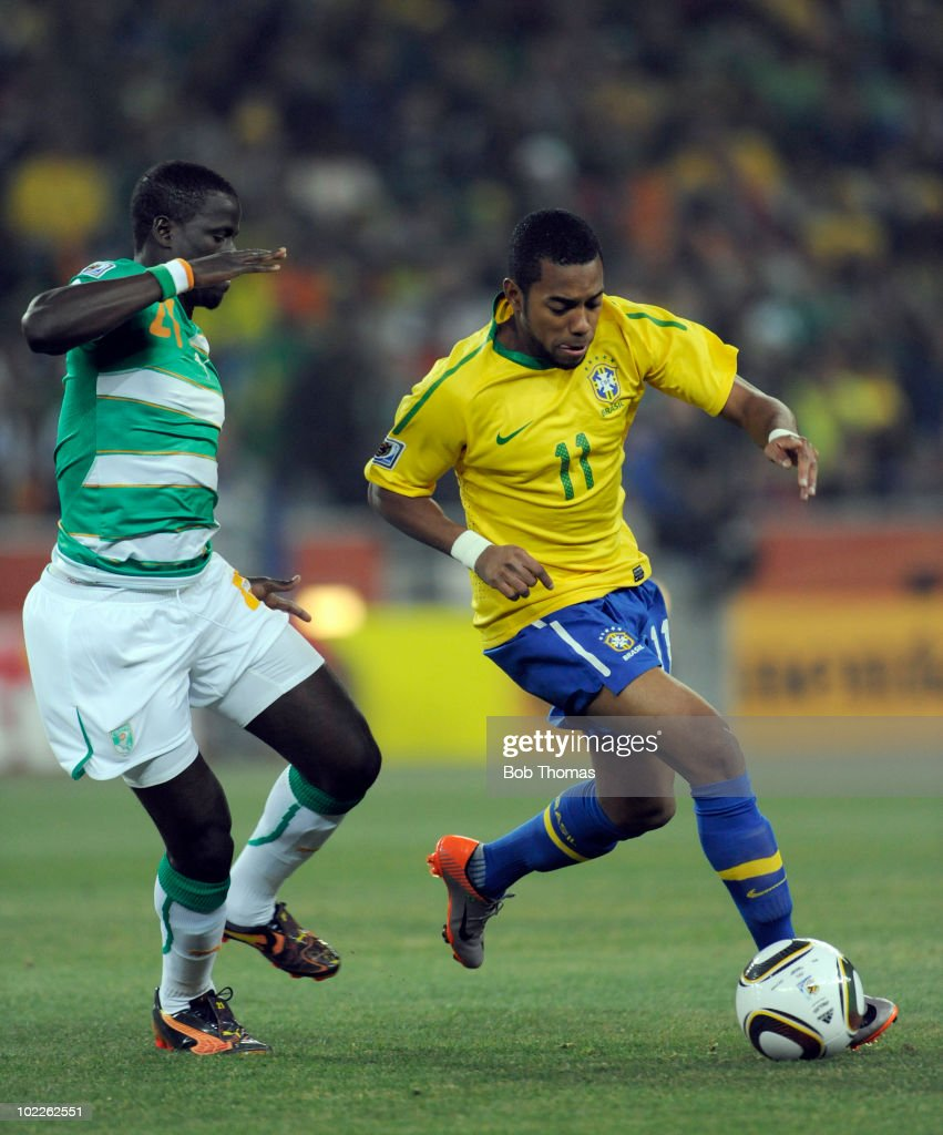 Robinho of Brazil challenged by Emmanuel Eboue of the Ivory Coast during the 2010 FIFA World Cup South Africa Group G match between Brazil and Ivory Coast at Soccer City Stadium on June 20, 2010 in Johannesburg, South Africa. Brazil won the match 3-1.