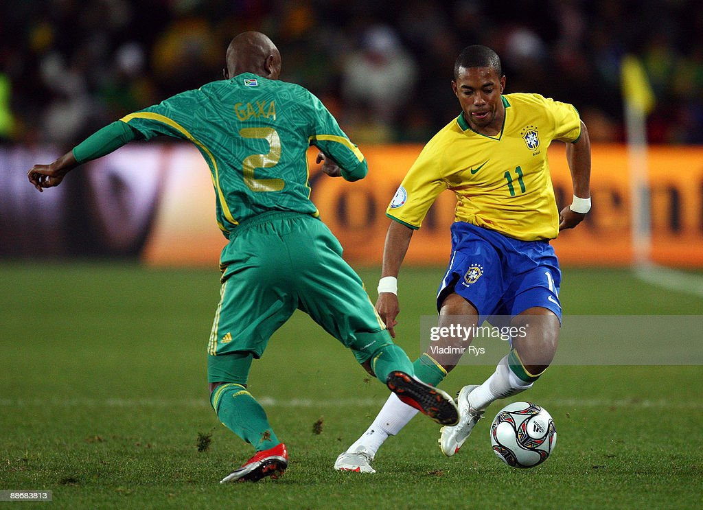 Robinho of Brazil competes with Siboniso Gaxa of South Africa during the FIFA Confederations Cup Semi Final match beween Brazil and South Africa at...