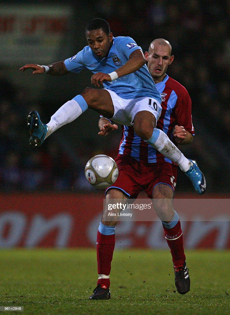 Robinho of Manchester City flicks the ball past Rob Jones of Scunthorpe United during the FA Cup sponsored by EON Fourth round match between...