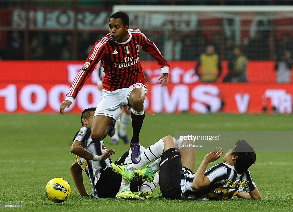 Robinho (L) of Milan leaps over a challenge from Marcelo Estegarribia of Juventus during the Serie A match between AC Milan and Juventus FC at Stadio Giuseppe Meazza on February 25, 2012 in Milan, Italy.