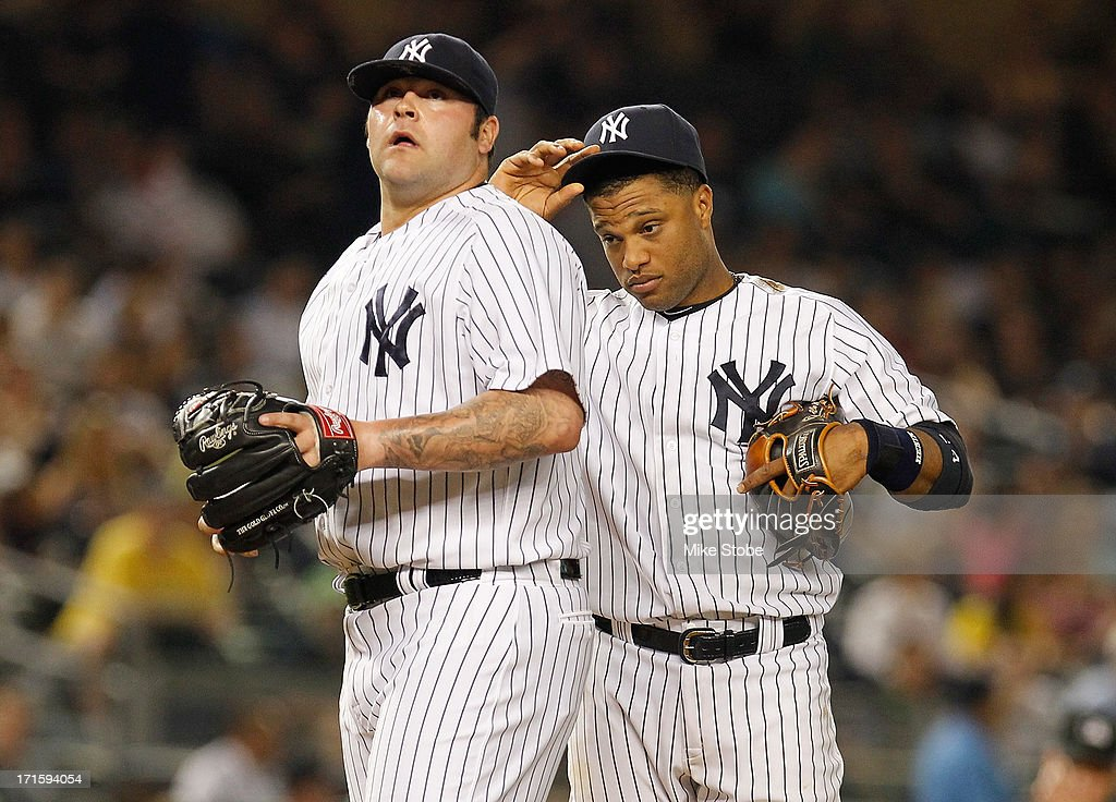 Robinson Cano #24 and Joba Chamberlain #62 of the New York Yankees looks in the seventh inning against the Texas Rangers on at Yankee Stadium on June 26, 2013 in the Bronx borough of New York City.