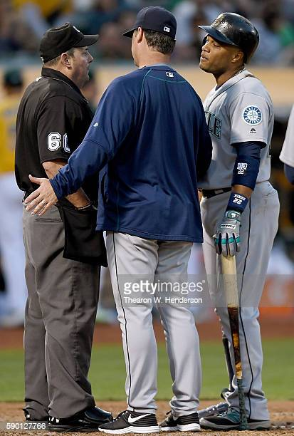 Robinson Cano and manager Scott Servais of the Seattle Mariners argues with home plate umpire Marty Foster that he fouled tipped a ball into the dirt...