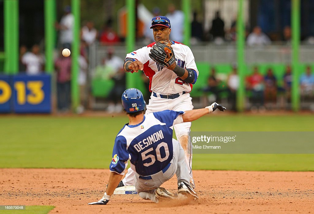 <a gi-track='captionPersonalityLinkClicked' href=/galleries/search?phrase=Robinson+Cano&family=editorial&specificpeople=538362 ng-click='$event.stopPropagation()'>Robinson Cano</a> #24 of the Dominican Republic turns a game ending double play as Stefano Desimoni #50 of Italy slides into second during a World Baseball Classic second round game at Marlins Park on March 12, 2013 in Miami, Florida.