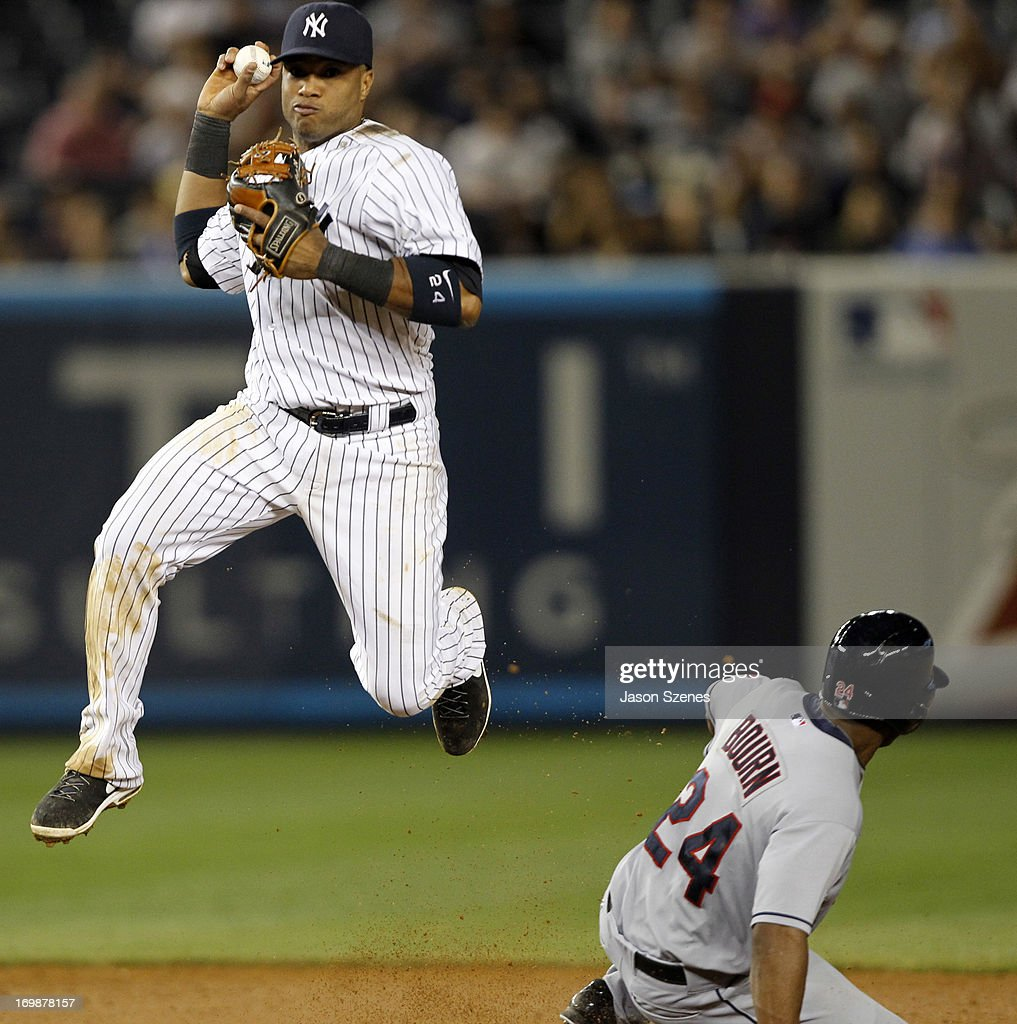 <a gi-track='captionPersonalityLinkClicked' href=/galleries/search?phrase=Robinson+Cano&family=editorial&specificpeople=538362 ng-click='$event.stopPropagation()'>Robinson Cano</a> #24 of the New York Yankees attempts to turn a double play on <a gi-track='captionPersonalityLinkClicked' href=/galleries/search?phrase=Michael+Bourn&family=editorial&specificpeople=835742 ng-click='$event.stopPropagation()'>Michael Bourn</a> #24 of the Cleveland Indians in the ninth at Yankees Stadium on June 3, 2013 in the Bronx borough of New York City. (Photo by Jason Szenes/Getty Images