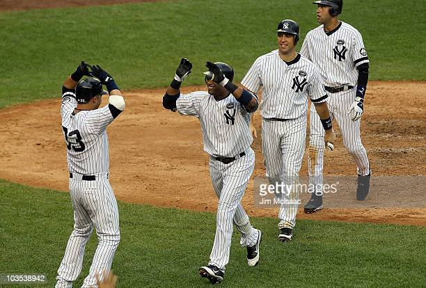 Robinson Cano of the New York Yankees celebrates his fifth inning grand slam home run against the Seattle Mariners with teammates Nick Swisher Mark...