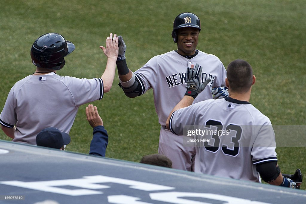 Robinson Cano #24 of the New York Yankees celebrates with Travis Hafner #33 after Cano hit a solo home run in the fifth inning against the Cleveland Indians on opening day at Progressive Field on April 8, 2013 in Cleveland, Ohio.