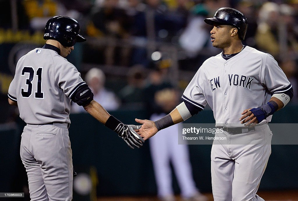 <a gi-track='captionPersonalityLinkClicked' href=/galleries/search?phrase=Robinson+Cano&family=editorial&specificpeople=538362 ng-click='$event.stopPropagation()'>Robinson Cano</a> #24 of the New York Yankees is congratulated by <a gi-track='captionPersonalityLinkClicked' href=/galleries/search?phrase=Ichiro+Suzuki&family=editorial&specificpeople=201556 ng-click='$event.stopPropagation()'>Ichiro Suzuki</a> #31 after Cano scored in the eighth inning against the Oakland Athletics at O.co Coliseum on June 11, 2013 in Oakland, California.