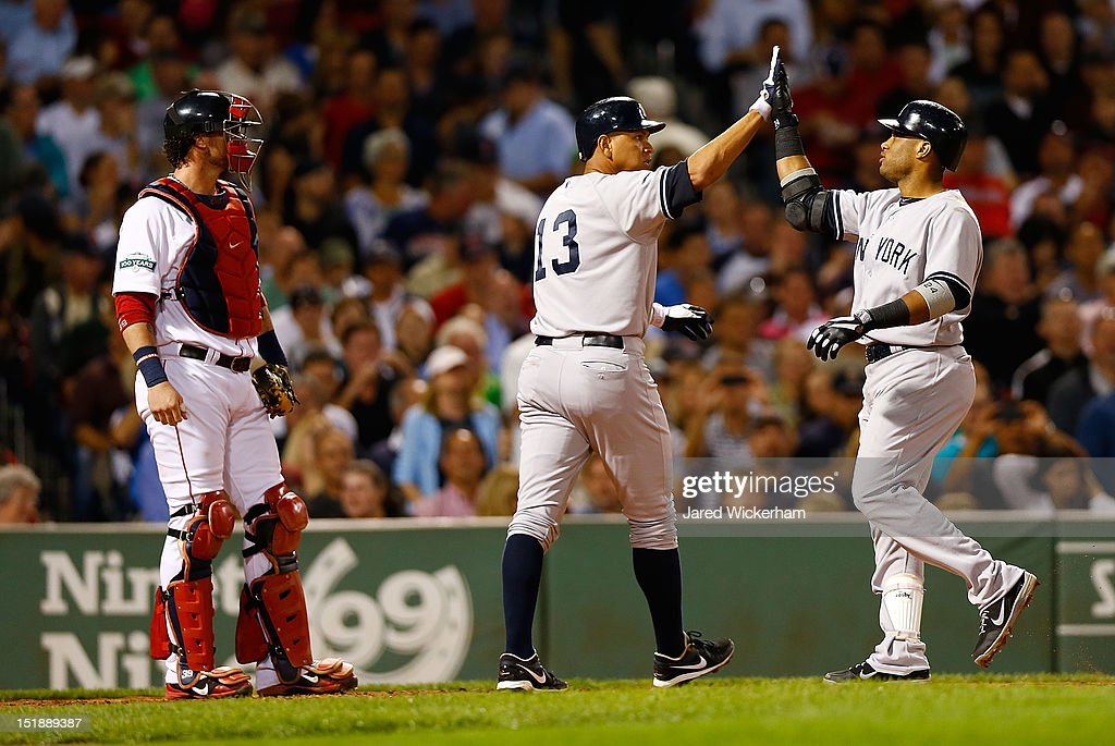 Robinson Cano #24 of the New York Yankees is congratulated by teammate Alex Rodriguez #13 after they both scored on Cano's home run in the fourth inning against the Boston Red Sox during the game on September 12, 2012 at Fenway Park in Boston, Massachusetts.