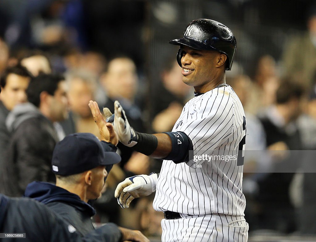 Robinson Cano #24 of the New York Yankees is congratulated by teammates in the dugout after his solo home run in the sixth inning the Arizona Diamondbacks on April 18, 2013 at Yankee Stadium in the Bronx borough of New York City.