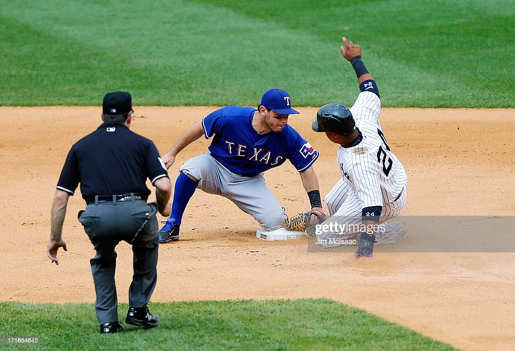Robinson Cano #24 of the New York Yankees is tagged out by Ian Kinsler #5 of the Texas Rangers trying to advance in the seventh inning at Yankee Stadium on June 27, 2013 in the Bronx borough of New York City.