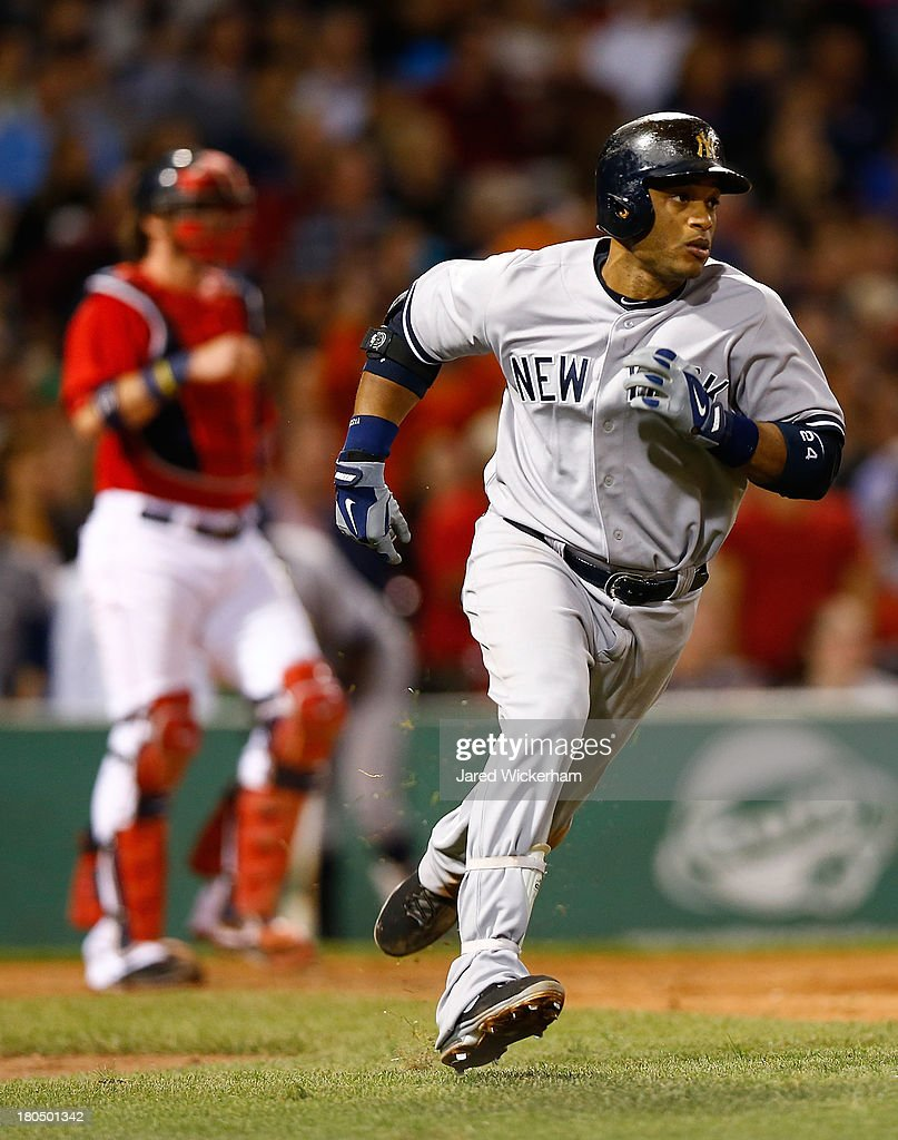 Robinson Cano #24 of the New York Yankees runs to first base after hitting a two-run triple in the 7th inning against the Boston Red Sox during the game on September 13, 2013 at Fenway Park in Boston, Massachusetts.