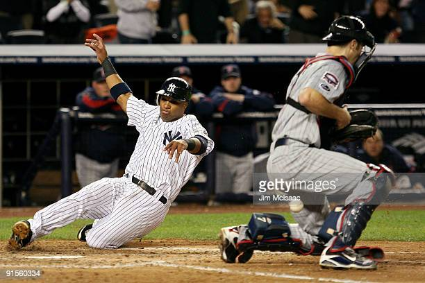 Robinson Cano of the New York Yankees slides into home to score a run past catcher Joe Mauer of the Minnesota Twins in the fourth inning of Game One...
