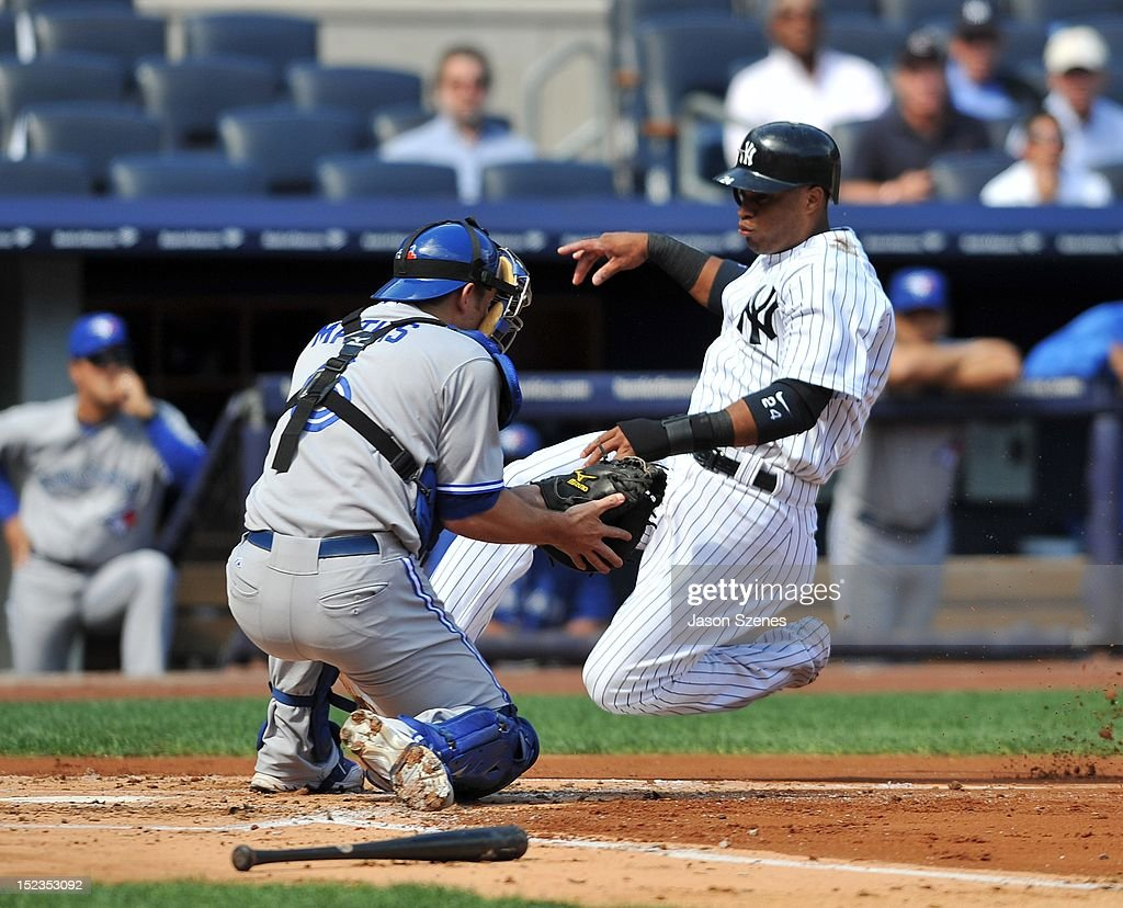 Robinson Cano #24 of the New York Yankees (L) slides safely past Toronto Blue Jays catcher Jeff Mathis at home plate in the first inning during the first game of a double header at Yankee Stadium on September 19, 2012 in the Bronx borough of New York City. (Photo by Jason Szenes/Getty Images