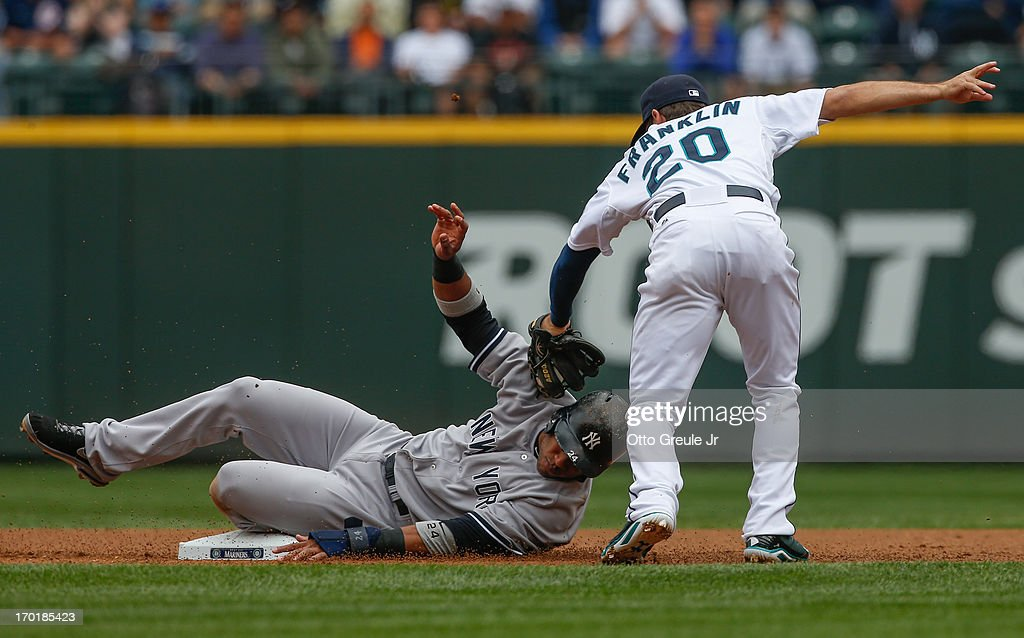 Robinson Cano #24 of the New York Yankees steals second base against second baseman Nick Franklin #20 of the Seattle Mariners at Safeco Field on June 8, 2013 in Seattle, Washington.