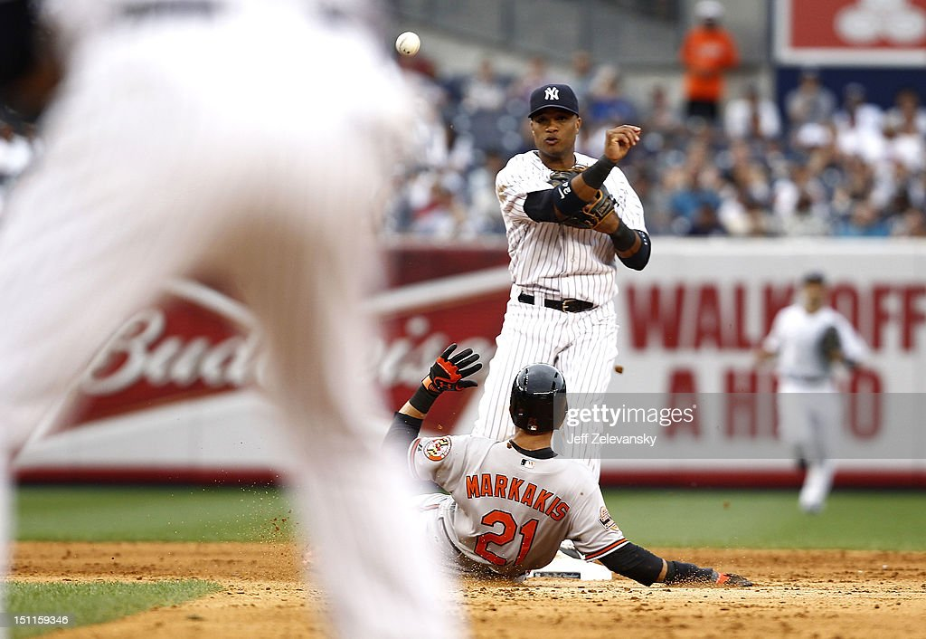 <a gi-track='captionPersonalityLinkClicked' href=/galleries/search?phrase=Robinson+Cano&family=editorial&specificpeople=538362 ng-click='$event.stopPropagation()'>Robinson Cano</a> #24 of the New York Yankees throws to first after forcing out <a gi-track='captionPersonalityLinkClicked' href=/galleries/search?phrase=Nick+Markakis&family=editorial&specificpeople=614708 ng-click='$event.stopPropagation()'>Nick Markakis</a> #21of the Baltimore Orioles at Yankee Stadium on September 2, 2012 in the Bronx borough of New York City.