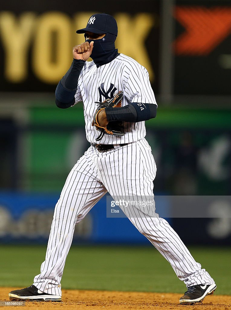 Robinson Cano #24 of the New York Yankees tries to stay warm during the game against the Boston Red Sox on April 3, 2013 at Yankee Stadium in the Bronx borough of New York City.