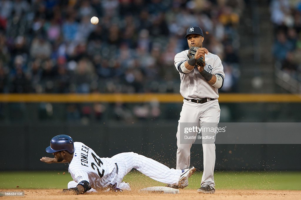 Robinson Cano #24 of the New York Yankees turns a double play past a sliding Dexter Fowler #24 of the Colorado Rockies in the fourth inning of a game at Coors Field on May 8, 2013 in Denver, Colorado.