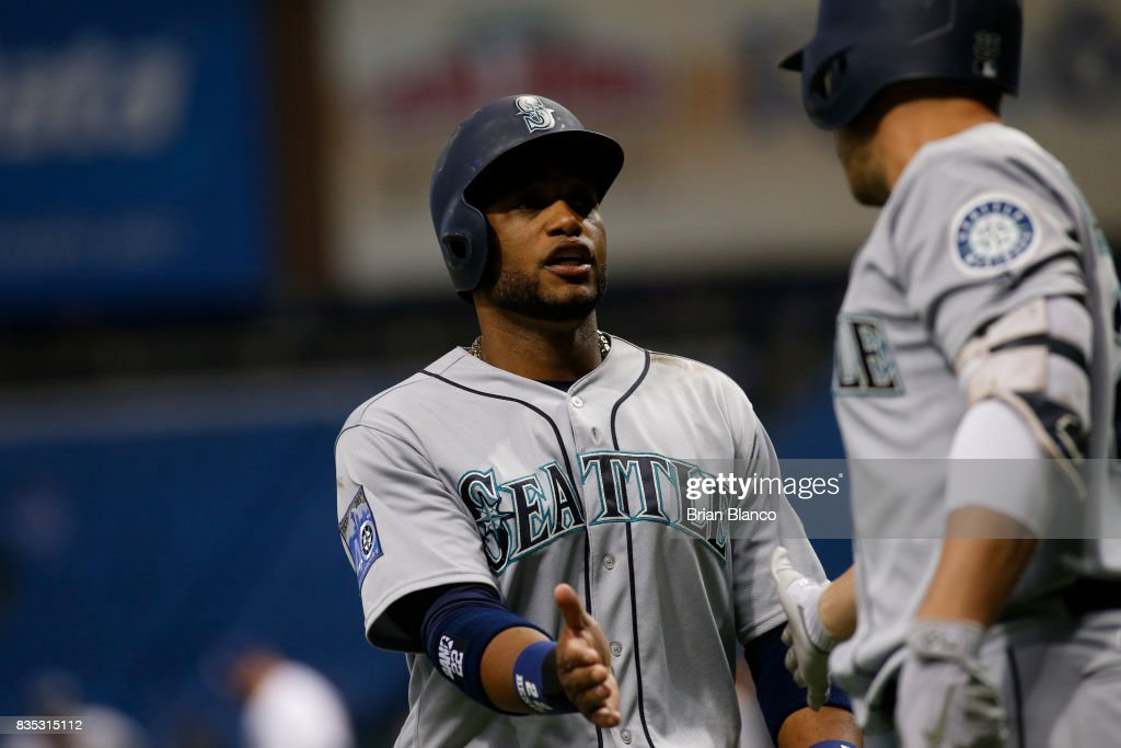 Robinson Cano #22 of the Seattle Mariners celebrates with teammate Danny Valencia #26 after scoring off of the throw after Kyle Seager grounded out to second baseman Daniel Robertson of the Tampa Bay Rays during the first inning of a game on August 18, 2017 at Tropicana Field in St. Petersburg, Florida.