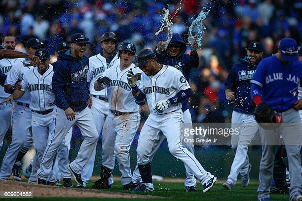 Robinson Cano of the Seattle Mariners celebrates with teammates after hitting a gamewinning sacrifice fly to beat the Toronto Blue Jays 21 in twelve...