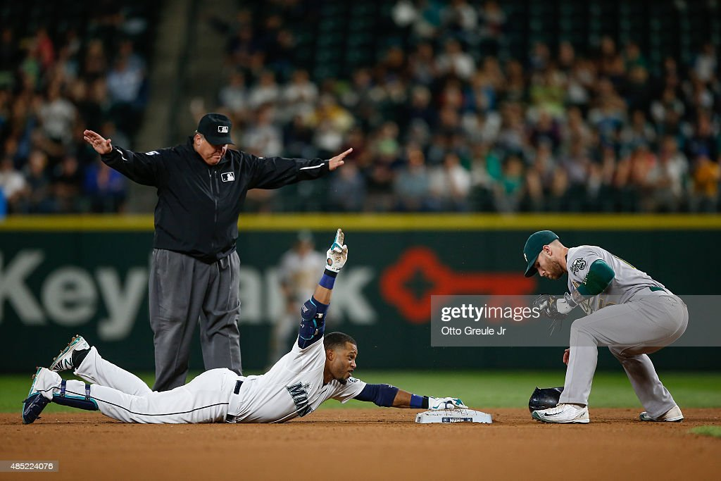Robinson Cano #22 of the Seattle Mariners gestures after doubling against second baseman Brett Lawrie #15 of the Oakland Athletics in the seventh inning at Safeco Field on August 25, 2015 in Seattle, Washington. The double gave Cano 30 for 11 consecutive seasons.