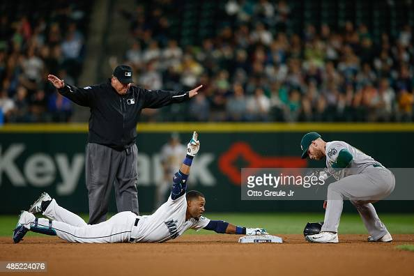 Robinson Cano of the Seattle Mariners gestures after doubling against second baseman Brett Lawrie of the Oakland Athletics in the seventh inning at...