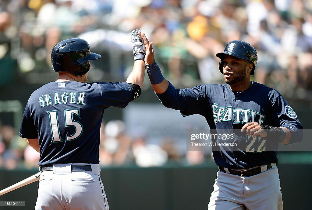 Robinson Cano #22 of the Seattle Mariners is congratulated by Kyle Seager #15 after Cano scored against the Oakland Athletics in the top of the third inning at O.co Coliseum on April 6, 2014 in Oakland, California. Cano scored on an RBI single from Justin Smoak.